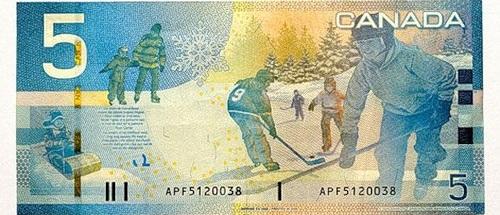 A Canadian bank note for five dollars, depicting children playing ice hockey