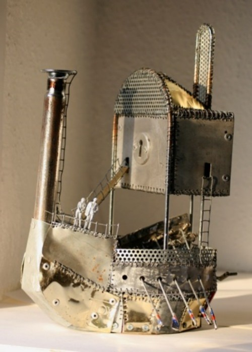 Small sculpture of a boat, made from recycled materials