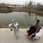 Farmer Wu Yulu, 48, rides in a cart pulled by his walking robot