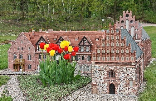 Tulips, like fabulous trees grow among the miniature architecture of the park