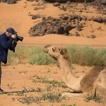 A photographer taking picture of a camel