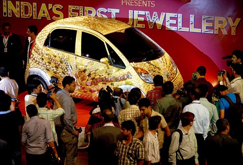 People stare at the Goldplus car covered in 80kg of 22 carat gold, 15kg of silver and 10,000 semi precious stones and gems