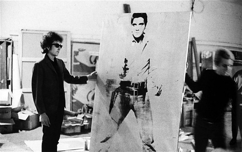 Bob Dylan holding the portrait of Elvis Presley by Andy Warhol in 1965.