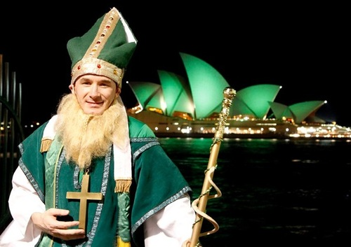 A man dressed as St Patrick poses for pictures as Sydney Opera House is lit with green lights during St Patrick's Day celebrations in central Sydney March 17, 2010