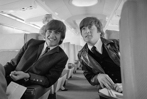 One half of the Beatles singing group, George Harrison and John Lennon, are shown aboard their plane here prior to taking off for London, England