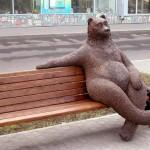 A bear sitting on a bench