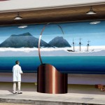 John inserts a passer-by into the mural painted in Santa Cruz, California, entitled Bay in a Bottle, who is watching the ocean scene