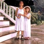 Enjoying the rain. Two girls under umbrella. Realism in paintings by American artist Steve Hanks