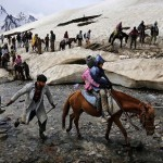 A Kashmiri horseman leads pilgrims on horseback across a stream during the journey to the Amarnath cave