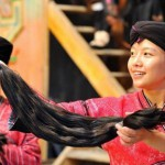 Proud Chinese woman demonstrates the lengh of woman's hair. Long haired women of Huangluo Yao, the Chinese village