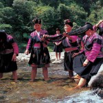 The village women gather at the river. Long haired Chinese women of the village Huangluo Yao