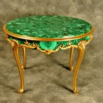 Malachite Table. Louis XV style malachite low table with carved giltwood legs and gallery. The malachite skirt is dressed with gilt metal mounts and the top is centered by a malachite floral design