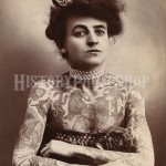 Photograph shows a half-length portrait of a woman with tattoos or body paint covering her arms and chest. 1907
