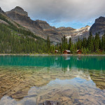 Mount Lefroy and Glacier peaks tower over the deluxe cabins reflecting in the turquoise waters of Lake O'Hara