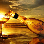 Wine glass and a bottle on the background of sunset
