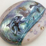 Dolphins playing in the sea. Made of mother-of-pearl