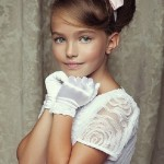 In a white dress and gloves, beautiful Russian child model Anastasia Bezrukova