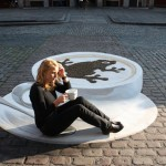 A girl looks like sitting on a saucer next to a cup of coffee on asphalt. 3-D illusion painted on a pavement. Creation by German artist Manfred Stader