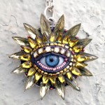 A pendant with human eye in the center. Jewelry sculpture covered with mosaic of bead