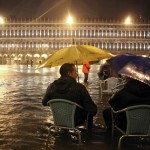 People sit on chairs in a flooded St Mark's Square at night during a period of seasonal high water in Venice November 1, 2012