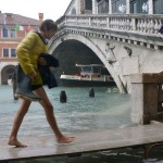 Photo of a young man walking in Venice during a period of seasonal high water