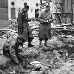 LIFE correspondent Percy Knauth sifting through the dirt & debris in the shallow shell hole where the bodies of Hitler and Eva Braun were thought to have been burned after their suicides, in the garden of the Reichstag. This photo was not originally published in LIFE