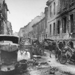 A man on bicycle and young boy going past smashed vehicles and abandoned artillery which fill Oberwallstrasse street, where some of the most bitter fighting for control of Berlin took place