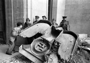 Russian soldiers and a civilian struggle to move a large bronze Nazi Party eagle that once loomed over a doorway of the Reich Chancellery, Berlin, 1945. This photo was not originally published in LIFE