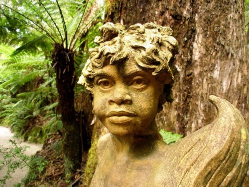 His sculptures of Aboriginal, set among the ferns represent the spirits of the land, expressing serenity and strength. They seem to grow out of the surrounding branches.