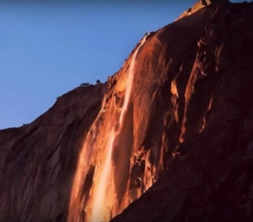 The setting sun illuminates the Horsetail Fall, making it glow orange and red