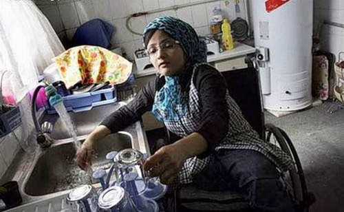 Housewife Fatima is washing dishes in the kitchen