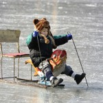A child rides a specially constructed ice-chair on the frozen Houhai Lake in Beijing