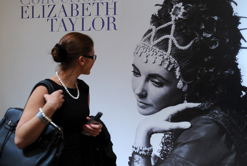 A woman looks at a poster of Elizabeth Taylor's jewelry public exhibition in GUM on Moscow's Red Square, on September 14, 2011