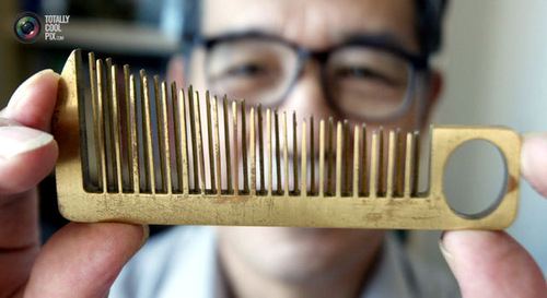 Han Yuzi, 63, inventor, holds up one of his creations, a hair comb that doubles as a small hand-held musical instrument. It measures 126.2 mm in length, 48.6 mm in width and weighs 68 grams