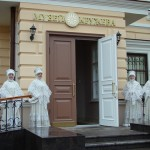 Women in beautiful handmade lace clothes standing at the entrance of the Museum of lace, Vologda