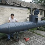 Tao Xiangli stands beside his homemade submarine. His submarine made from old oil barrels but fully functional with a periscope, depth control tanks, electric motors and two propellers