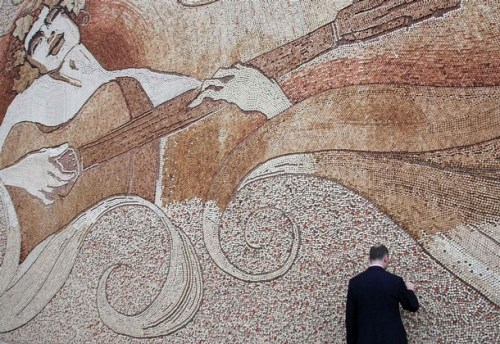 """Romeo with a crown of grapes playing the guitar while dancing with the sea and the sun"". A man looks at the largest mosaic in Tirana September 4, 2008"