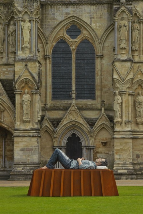 A man having a rest on the lawn in front of cathedral. If not his gigantic size, the man would look real. Surreal art installation by British sculptor Sean Henry