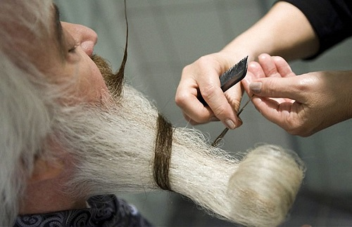 Stylist working with a participant of world Beard Moustache Championship in Trondheim, Norway