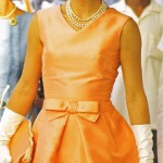 Jackie Kennedy wearing a fitted silk apricot dress and triple strand of pearls, walking through crowds at Udaipur during visit to India