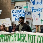 Kumi Naidoo, Executive Director of Greenpeace International, helps hold a banner at the front of a march with community activists near the Fisk Coal Power Station in a Moving Planet global day of action