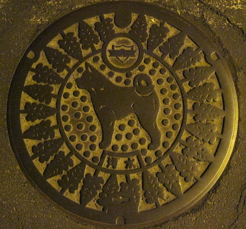 Akita inu, national Japanese dog depicted on manhole cover