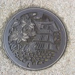 Traditional motif of Manhole cover decoration – blooming flowers and Japanese architecture