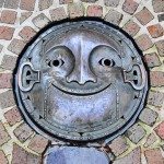 One-of-a-kind smiling face steam punk manhole cover