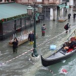 Pedestrians wade through flood waters, past a gondola, in Venice December 1, 2008