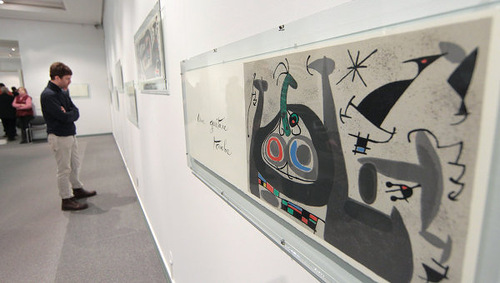 A visitor looks at the exhibition of Salvador Dali's colorful illustration for Alice in Wonderland
