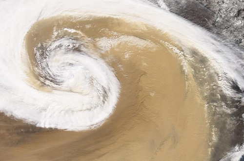 The image of a dust storm as it swirled over China in April of 2001. A strong temperate cyclone spun counter-clockwise over China, pushing a wall of dust as it moved. The Earth Observatory Photographs