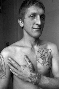 The tattoo on the chest is a 'grin' at the authorities, the text above and below reads 'If I can't crush them with my strength / I will crush them with my rage'.