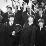 1964-Kennedy Airport, New York, New York- The Beatles wave to the thousands of screaming teenagers after their arrival at JFK Airport
