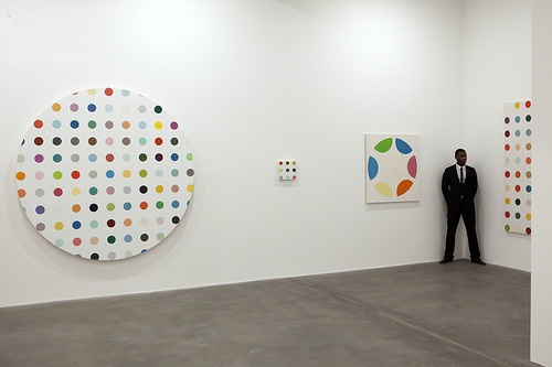 A security guard stands near paintings by Damien Hirst at Gagosian Gallery in London